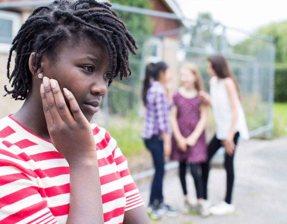 African American girl think to herself, while group of girls gossip in background.