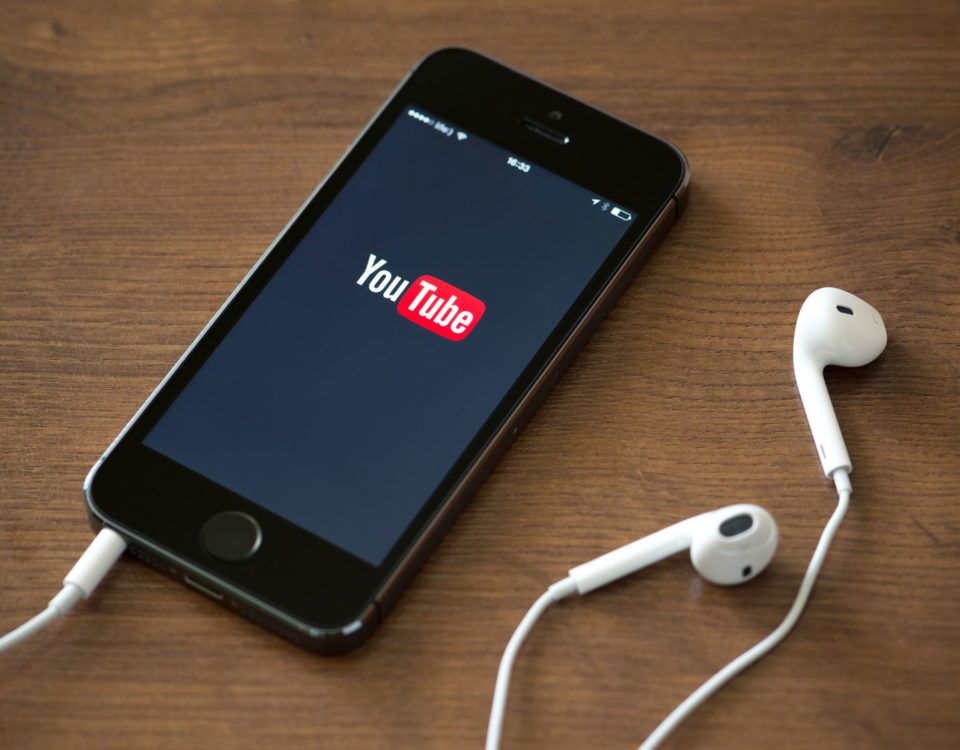 iPhone and headphones showing the YouTube app